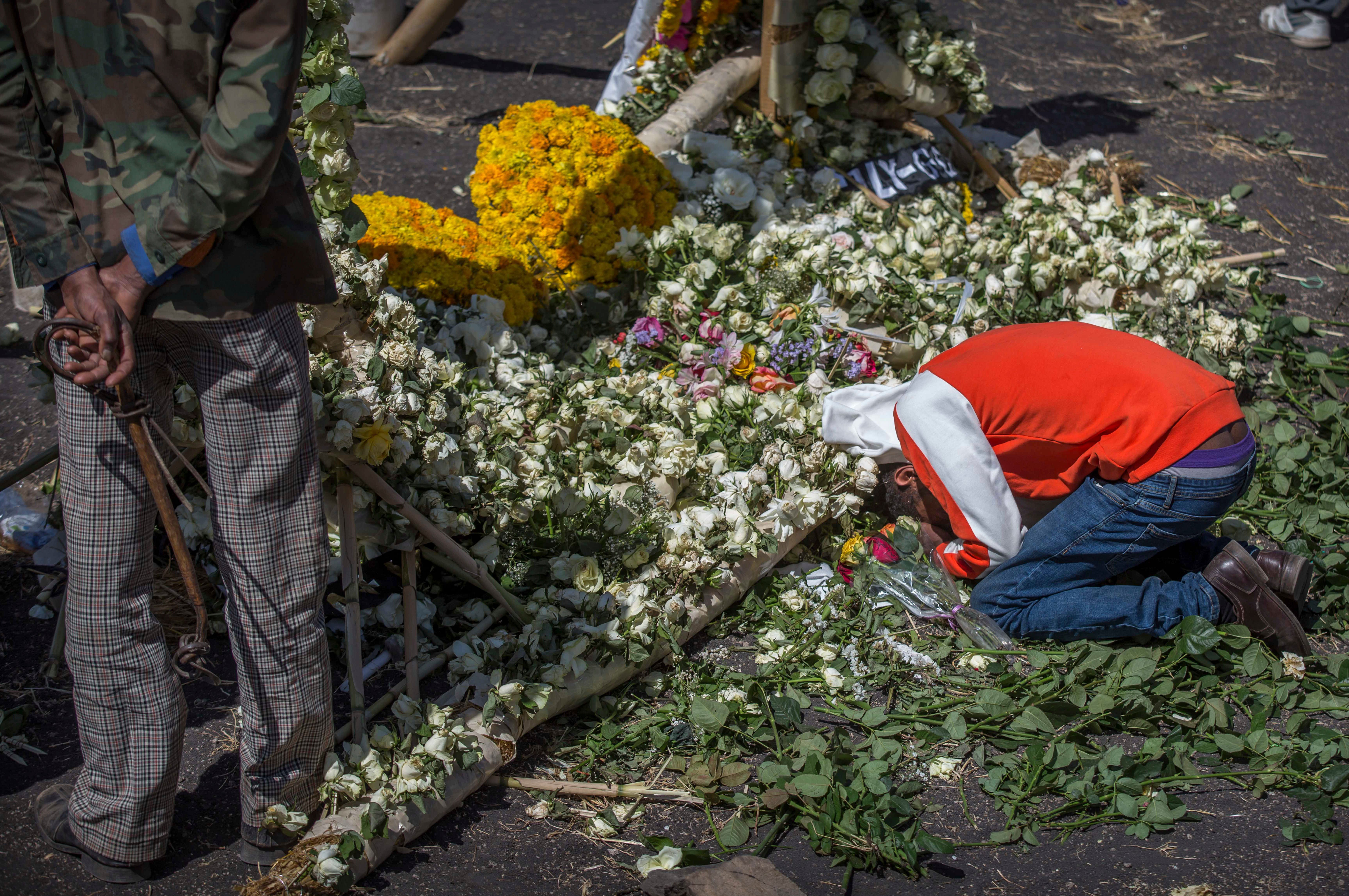 A relative of a crash grieves next to a floral tribute at the scene where the Ethiopian Airlines Boeing 737 Max 8 crashed shortly after takeoff March 10, killing all 157 on board.