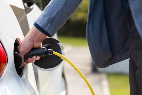 Charging of the electric car. Businessman's hand holding the electric cable to the car. Car features have been changed.