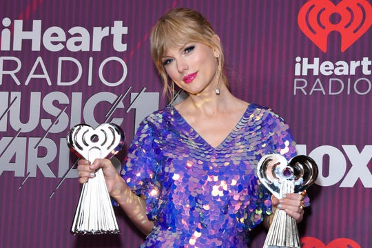 Taylor Swift in the iHeartRadio Music Awards press room with a trophy in each hand on March 14, 2019 in Los Angeles, California.