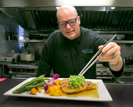 Ohana Grill chef and co-owner James Costello puts the final touches on pecan-crusted salmon with maple honey butter over sweet potato puree   at the Lavallette restaurant Friday night, March 15, 2019.
