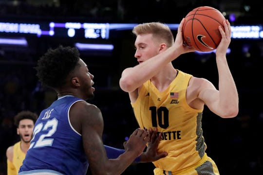 Marquette forward Sam Hauser, right, is defended by Seton Hall guard Myles Cale (22)