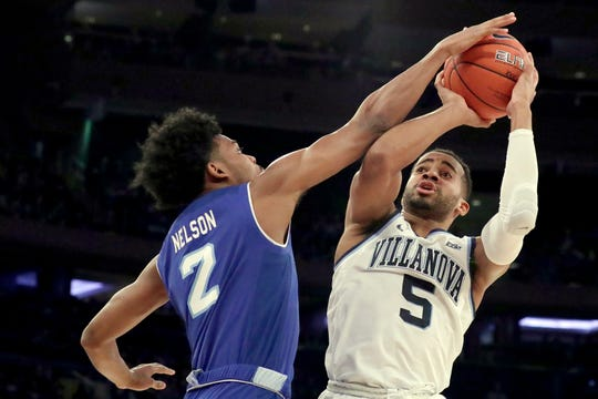 Villanova guard Phil Booth (5) goes up for a shot against Seton Hall guard Anthony Nelson (2)