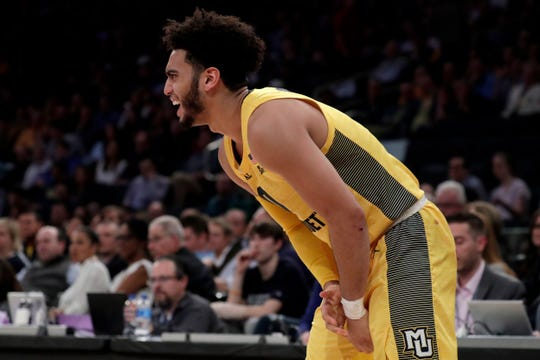 Marquette guard Markus Howard grabs at his wrist during the first half.
