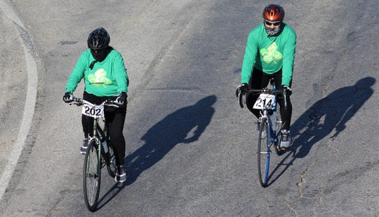 Lacey Boyd (202) and Johnny Rosas (214) cast shadows as they start Saturday's Steam N Wheels bike ride E.S. 11th Street heading east.