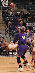 Lamar's Chastadie Barrs, left, draws a charge as ACU's Alyssa Adams drives to the basket.