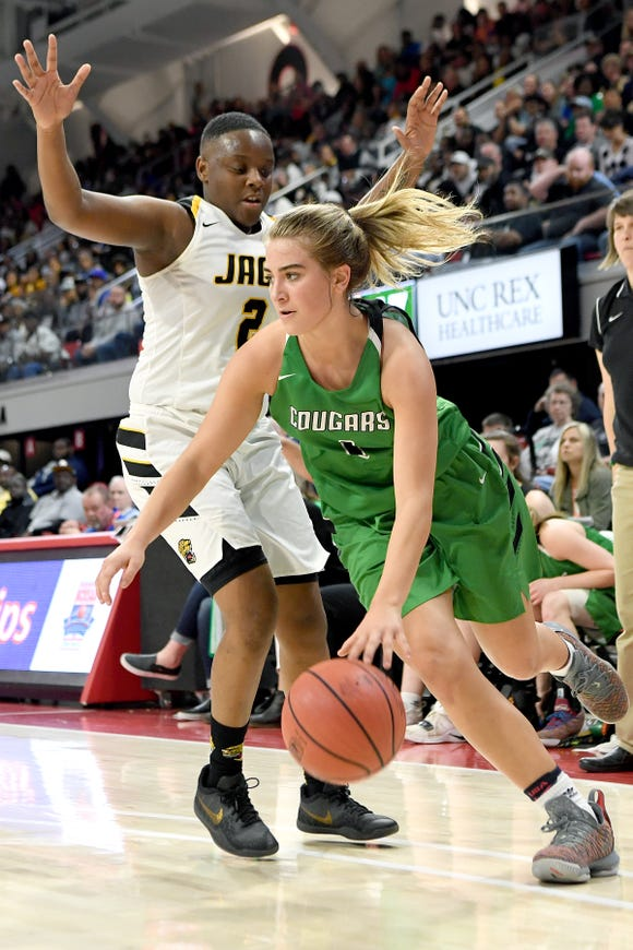 Mountain Heritage's Hannah Tipton pushes her way around Farmville Central's Jordan Joyner during the NCHSAA 2A state championship game at N.C State's Reynolds Coliseum on March 16, 2019. The Lady Cougars ended their perfect season as state champions with a 63-53 win.