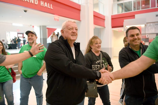 Dean Hicks, coach of the 1981 Mountain Heritage girls basketball team, shakes hands with fans before the NCHSAA 2A state championship game at N.C State's Reynolds Coliseum on March 16, 2019. Saturday was the first time the Lady Cougars played in the state final since Hicks' 1981 team.