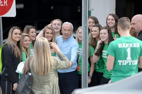 The Mountain Heritage girls basketball team takes a photo with UNC basketball coach Roy Williams after running into him on the street before the NCHSAA 2A state championship game at N.C State's Reynolds Coliseum on March 16, 2019.