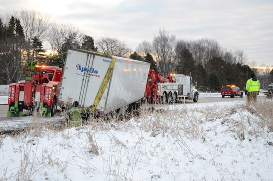 Workers remove a damaged semi along eastbound I-94 Saturday after several crashes.