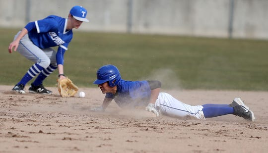 Bremerton's Hector Infante slides safely into second base against the Olympic Trojans at Legion Field in Bremerton on Friday, March 15, 2019.