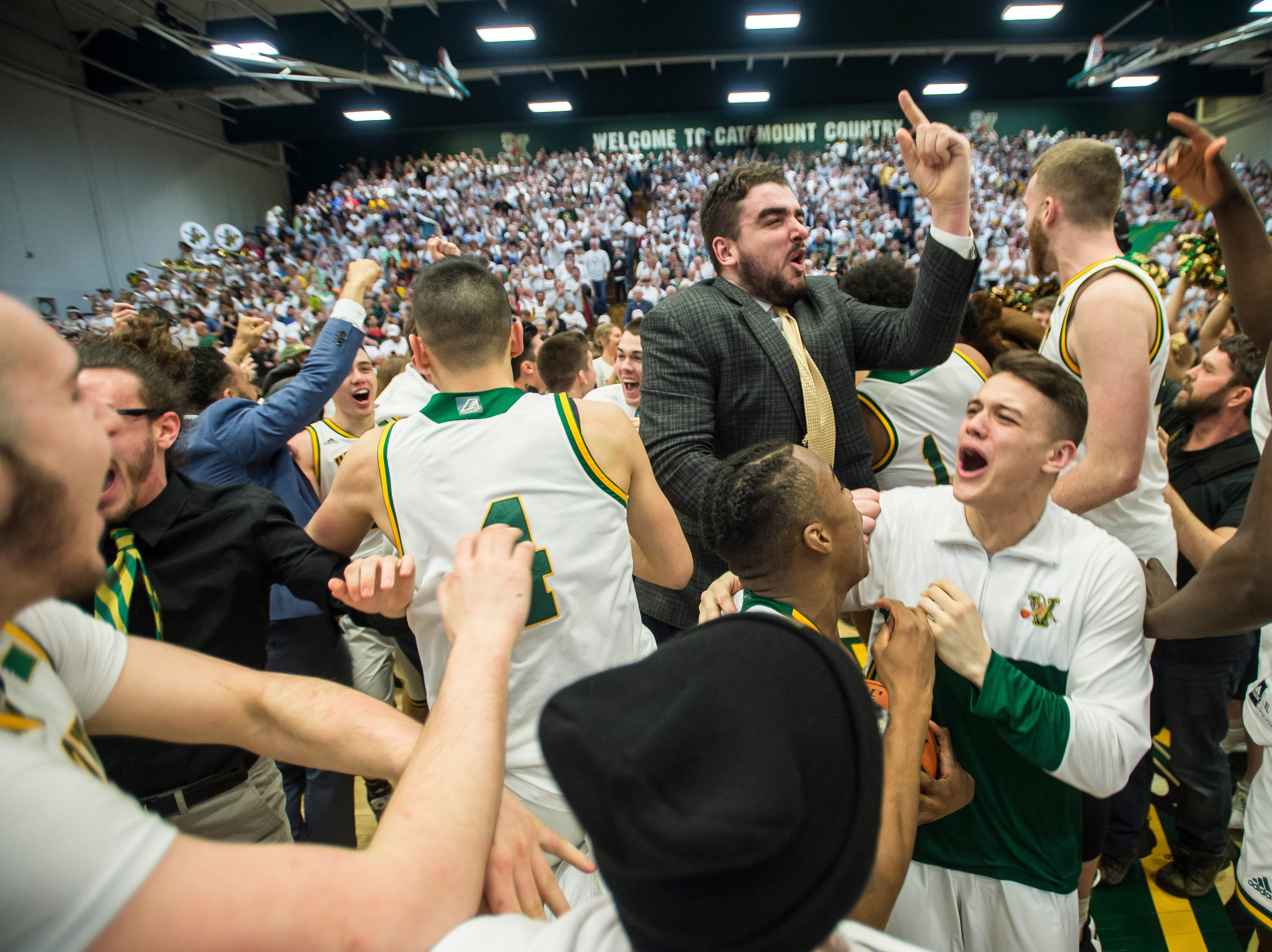 The UVM men's basketball team celebrates after winning the America East Championship in Burlington, Vt., on Saturday, March 16, 2019. UVM won 66-49 and will head to the NCAA March Madness Tournament.
