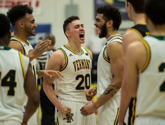 UVM Men's basketball #20 Ernie Duncan celebrates with #3 Anthony Lamb and teammates in the final seconds of the America East Championship in Burlington, Vt., on Saturday, March 16, 2019. UVM won, 66-49 and will head to the NCAA March Madness Tournament.