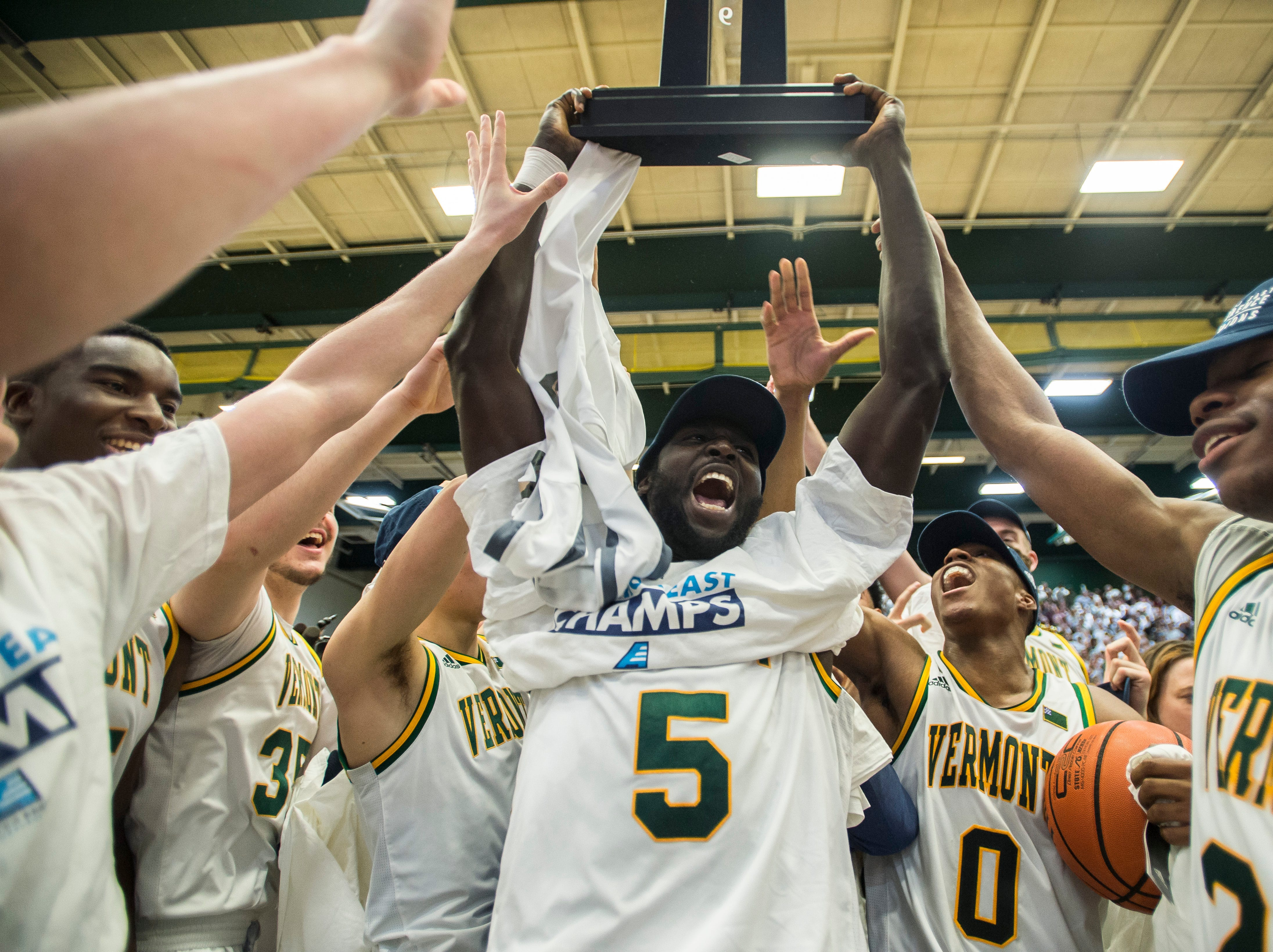 UVM men's basketball #5 Sam Dingba holds up the America East Championship trophy after winning over UMBC in Burlington, Vt., on Saturday, March 16, 2019. UVM won 66-49 and will head to the NCAA March Madness Tournament.