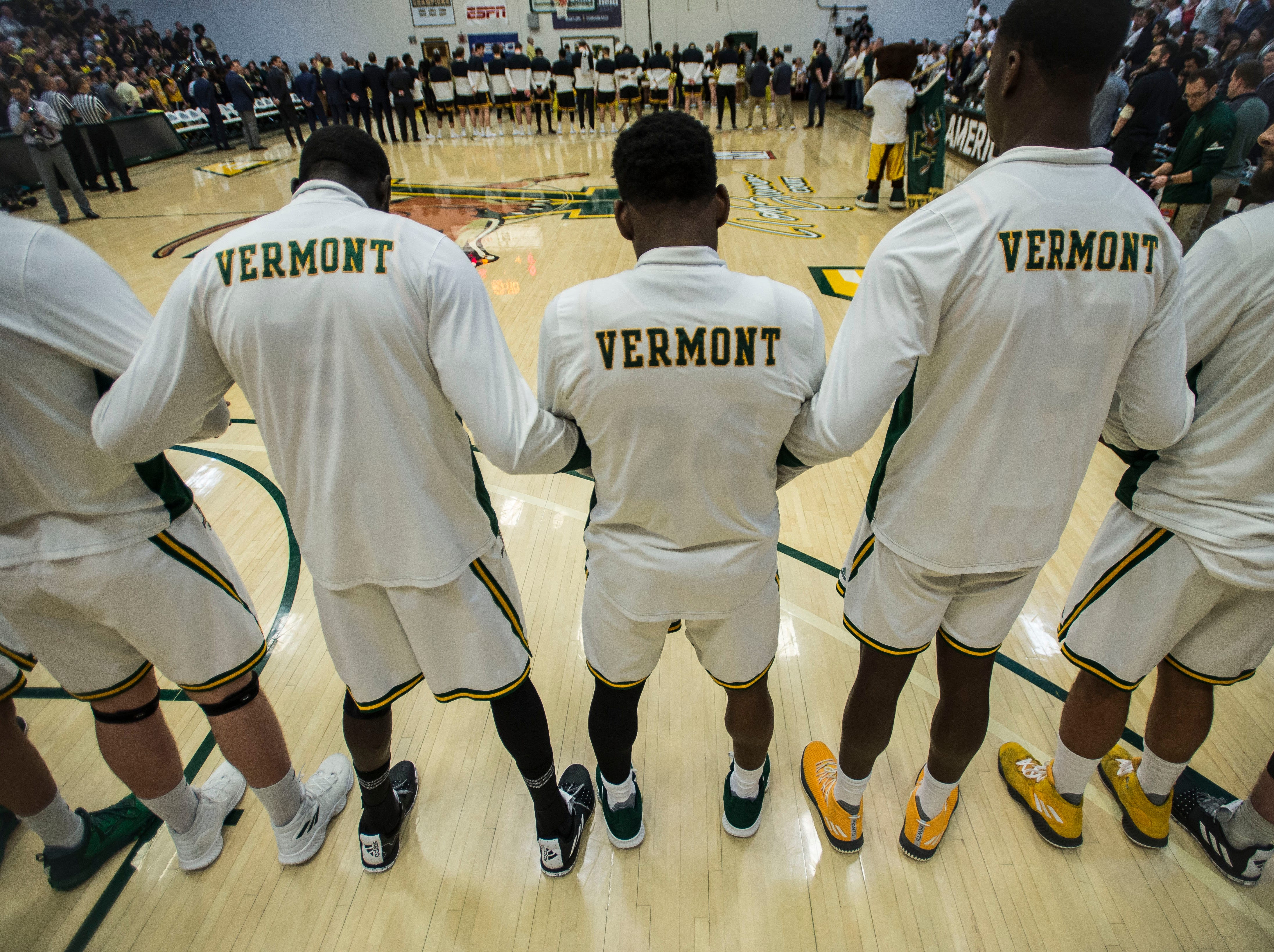 UVM Men's basketball team locks arms during the playing of the National Anthem before the start of the America East Championship in Burlington, Vt., on Saturday, March 16, 2019. UVM won, 66-49 and will head to the NCAA March Madness Tournament.