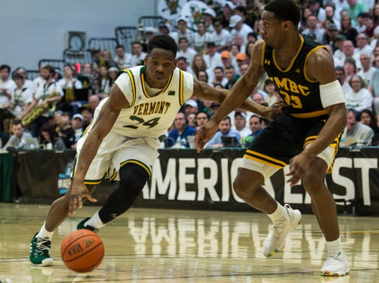 UVM Men's basketball #24 Ben Shungu drives past UMBC #33 Arkel Lamar during the America East Championship in Burlington, Vt., on Saturday, March 16, 2019. UVM won, 66-49 and will head to the NCAA March Madness Tournament.