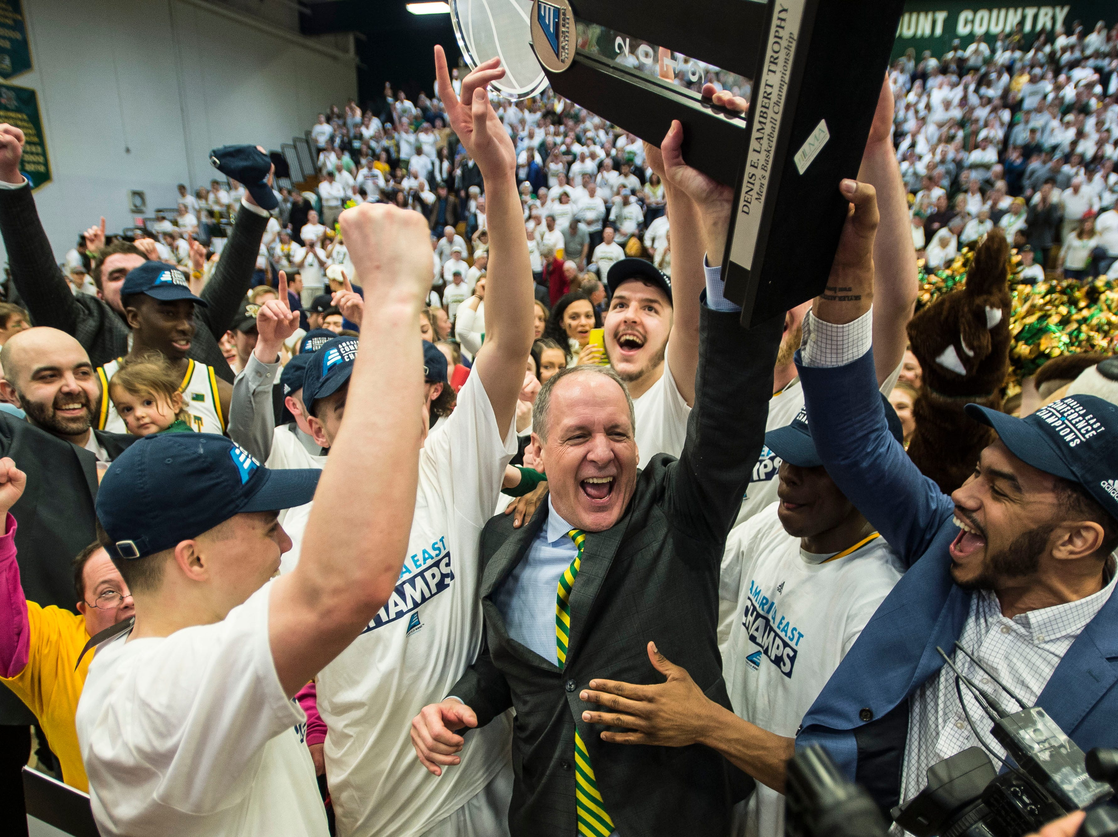 UVM Men's basketball Head Coach John Becker celebrates with his team during the America East Championship in Burlington, Vt., on Saturday, March 16, 2019. UVM won, 66-49 and will head to the NCAA March Madness Tournament.