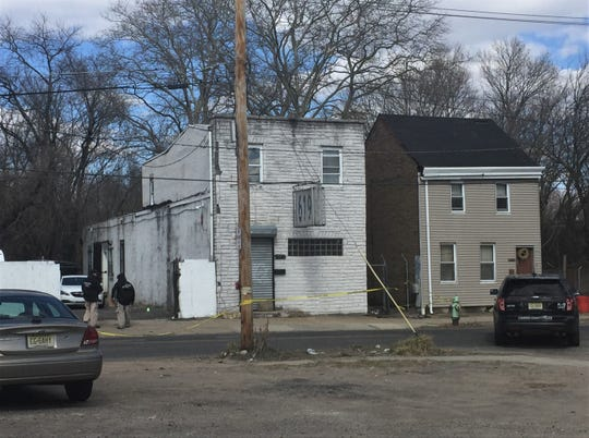 Investigators approach a building on the 600 block of Ferry Avenue in Camden where a man was shot dead early Saturday.