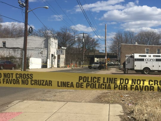 Police tape marks the scene of a Ferry Avenue shooting that killed a man and wounded three people early Saturday.