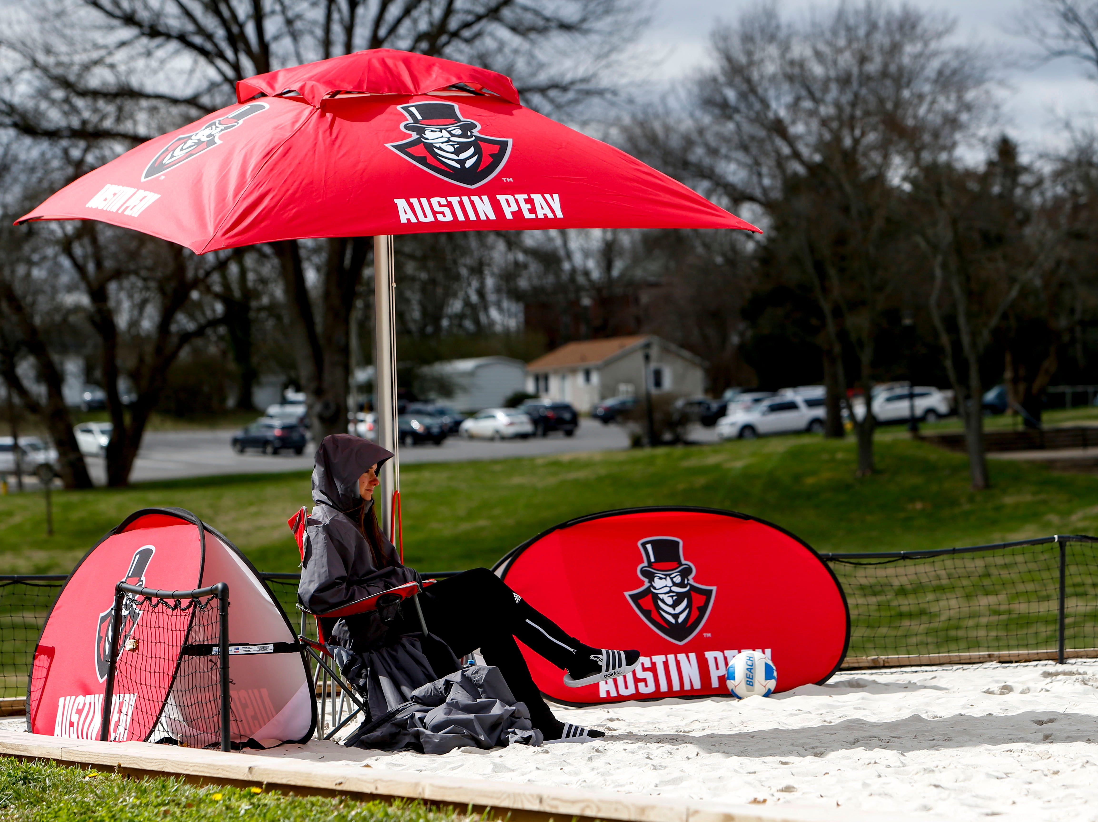 A coach watches from the sideline underneath the shade of an umbrella at Winfield Dunn Center lawn in Clarksville, Tenn., on Friday, March 15, 2019.