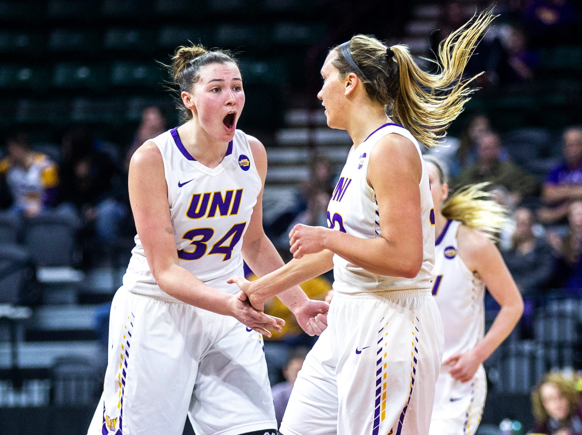 Northern Iowa forward Taylor Hagen (34) celebrates with Northern Iowa forward Heidi Hillyard, right, heading into a time out during a NCAA Missouri Valley Conference women's basketball quarterfinal tournament game, Friday, March 15, 2019, at the TaxSlayer Center in Moline, Illinois.