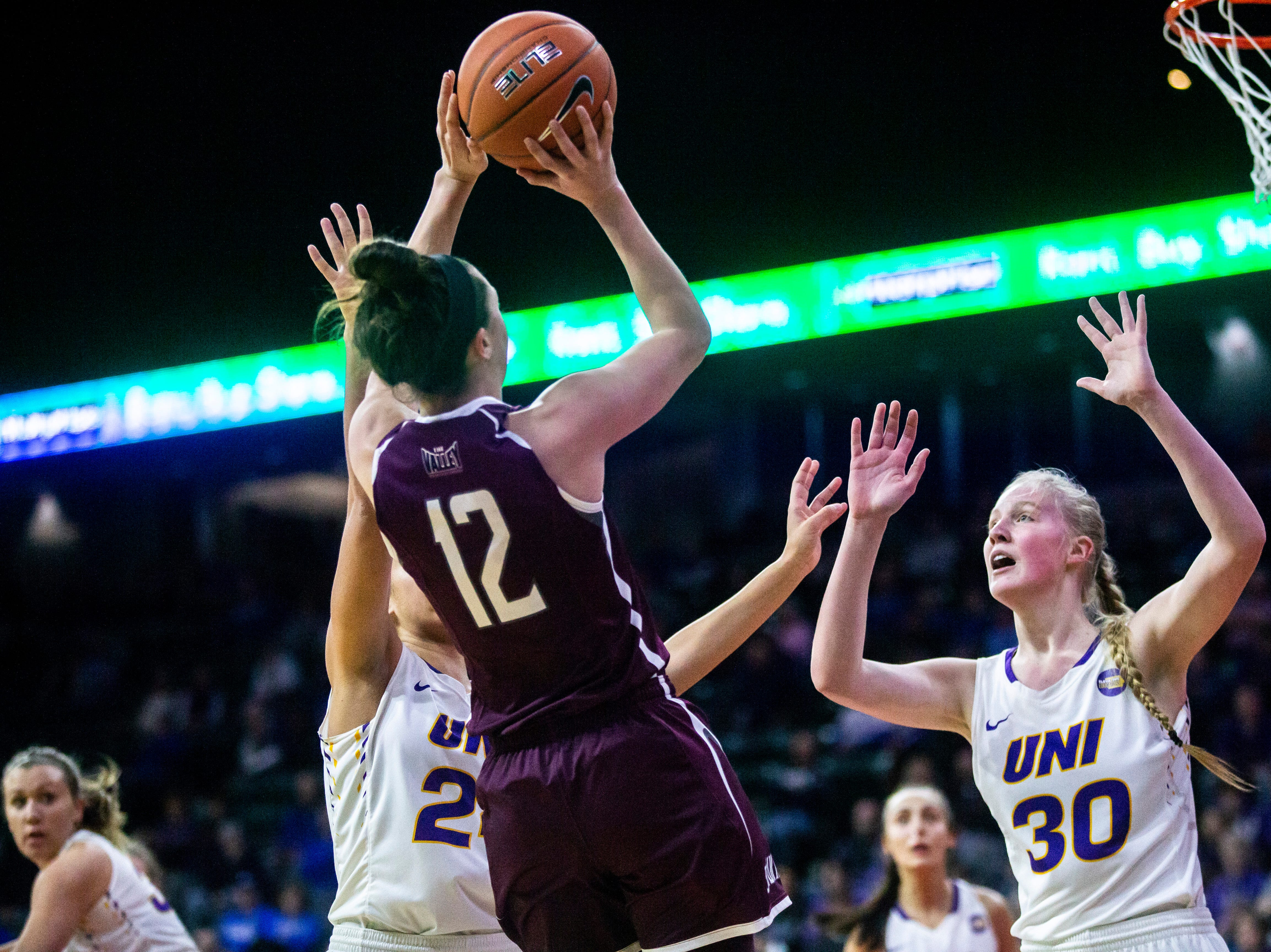Northern Iowa center Cynthia Wolf (30) and Northern Iowa guard Mikaela Morgan, left, defend Southern Illinois guard Makenzie Silvey (12) during a NCAA Missouri Valley Conference women's basketball quarterfinal tournament game, Friday, March 15, 2019, at the TaxSlayer Center in Moline, Illinois.