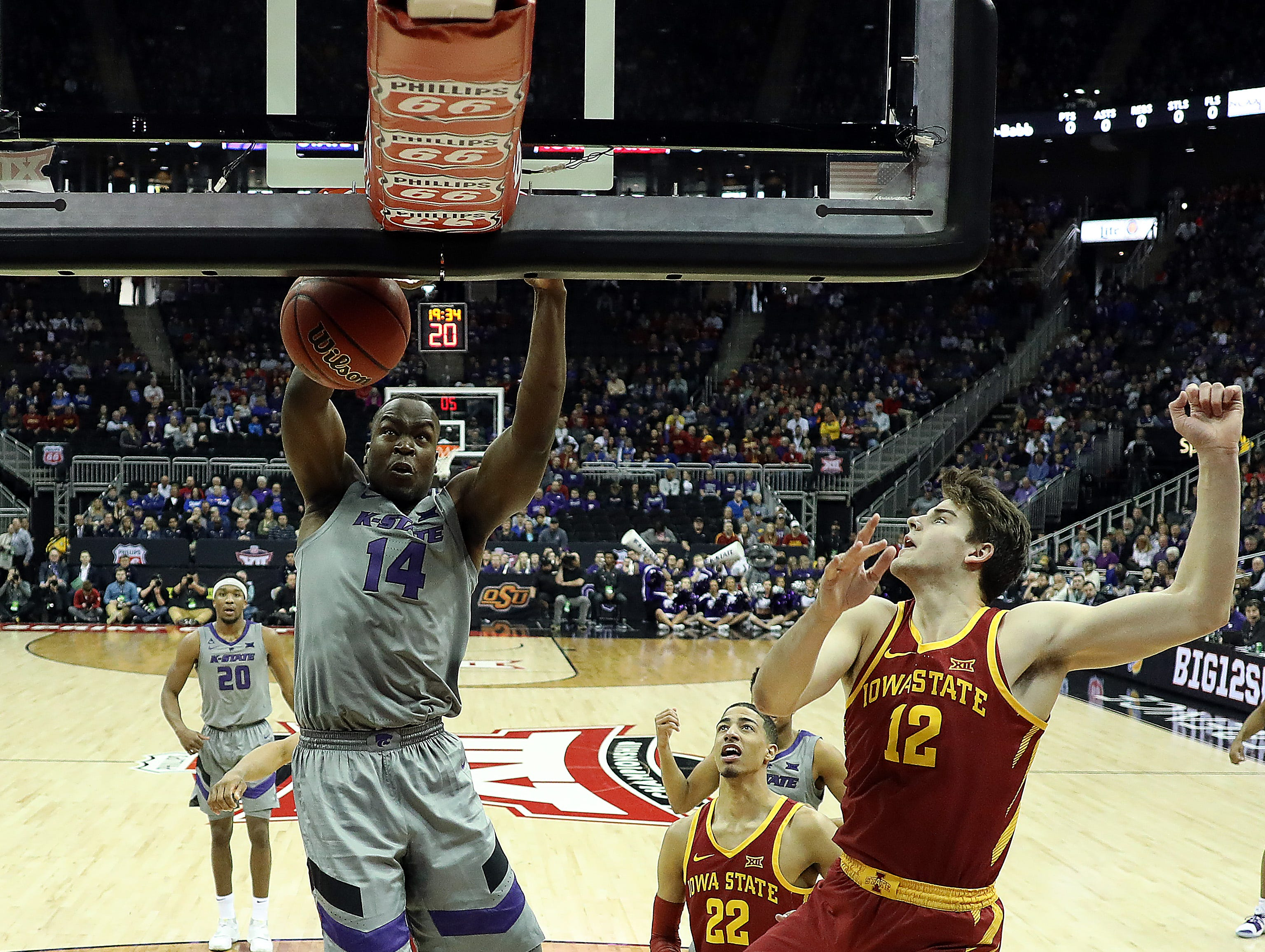 KANSAS CITY, MISSOURI - MARCH 15:   Makol Mawien #14 of the Kansas State Wildcats dunks as Michael Jacobson #12 of the Iowa State Cyclones defends during the semifinal game of the Big 12 Basketball Tournament at Sprint Center on March 15, 2019 in Kansas City, Missouri. (Photo by Jamie Squire/Getty Images)