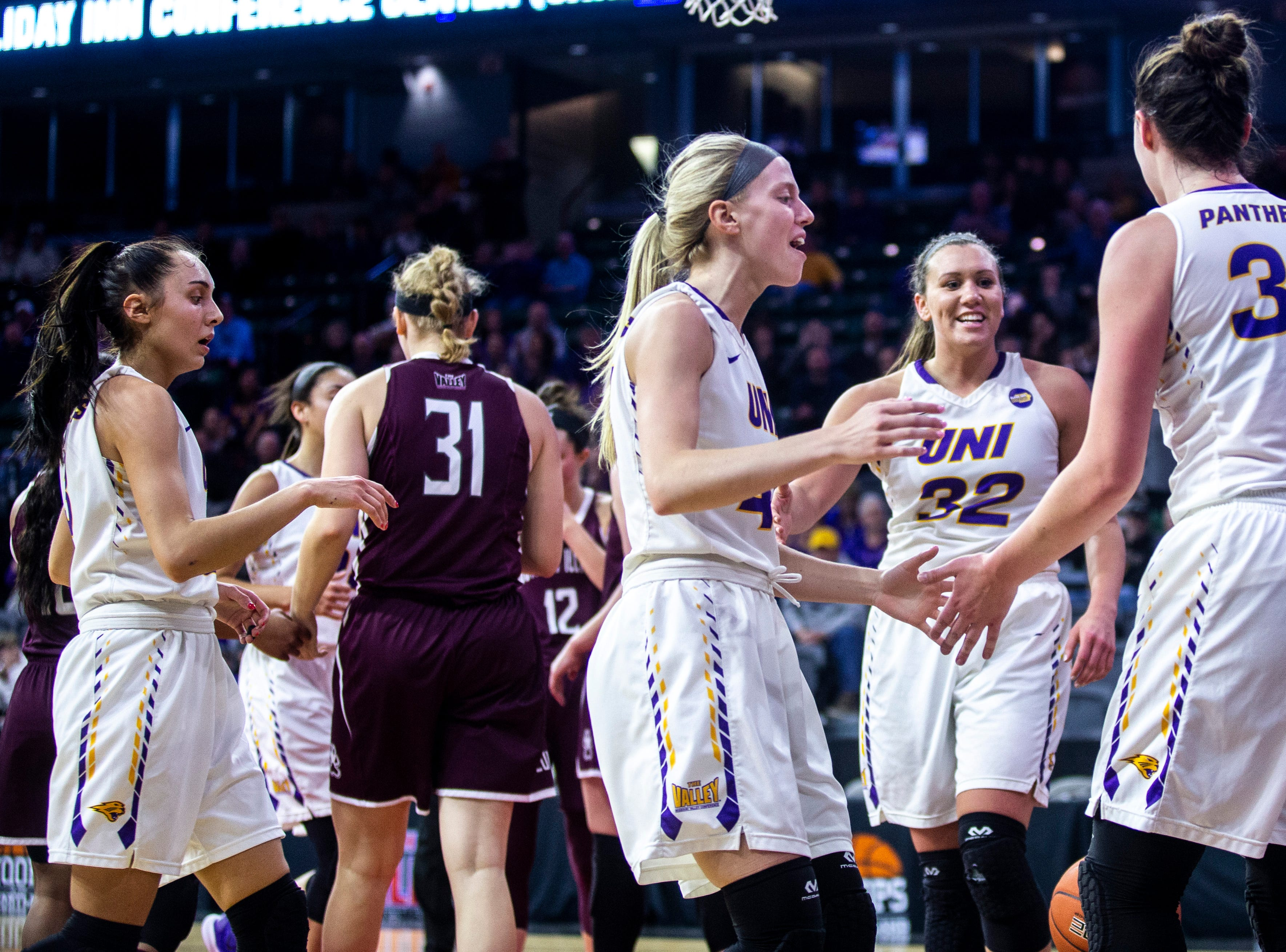 Northern Iowa forward Taylor Hagen (34) gets embraced by teammates, from left, Karli Rucker Abby Gerrits and Heidi Hillyard (32) after drawing a foul during a NCAA Missouri Valley Conference women's basketball quarterfinal tournament game, Friday, March 15, 2019, at the TaxSlayer Center in Moline, Illinois.