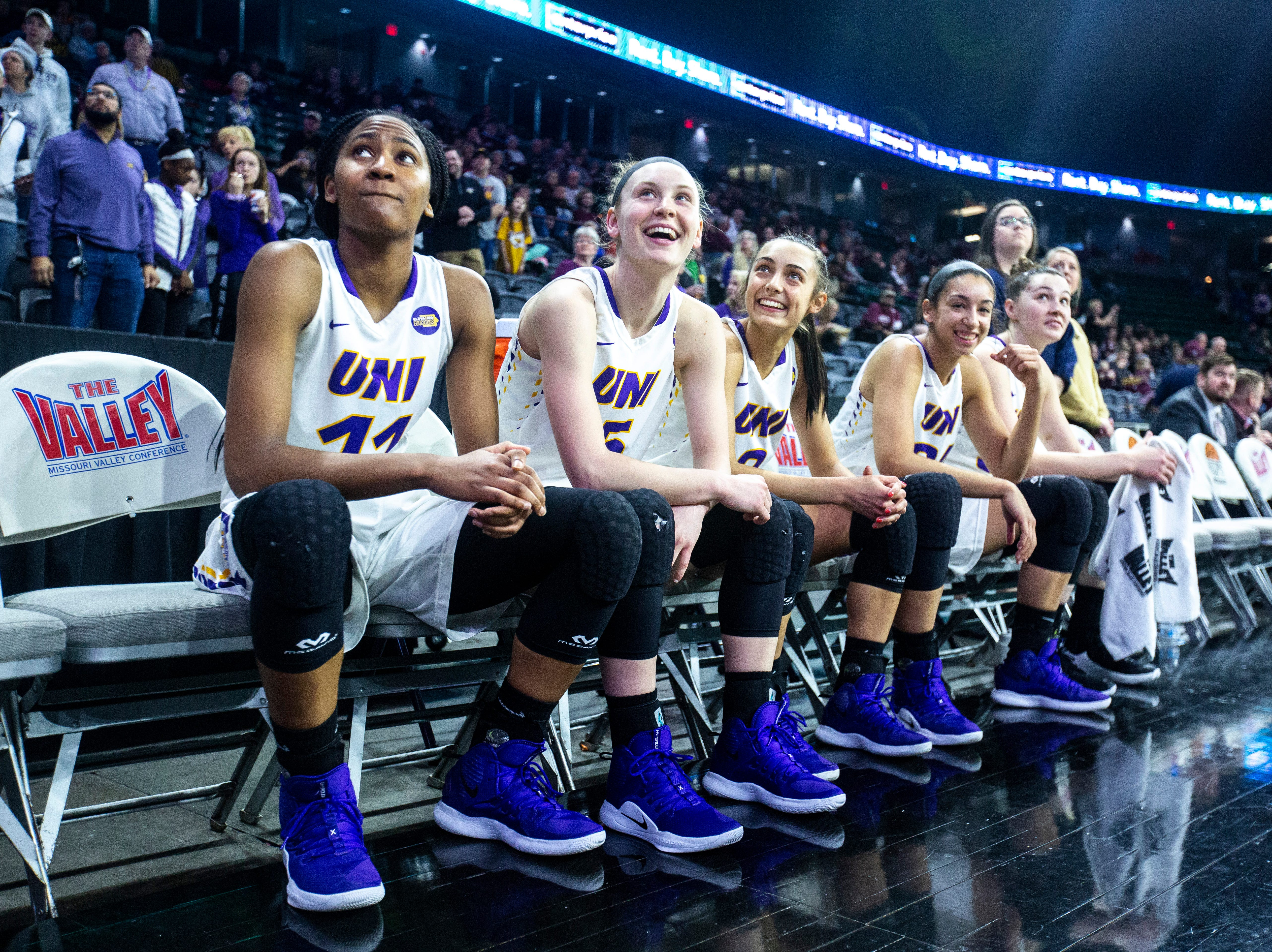 Northern Iowa Panthers, from left, Bre Gunnels, Nicole Kroeger, Karli Rucker, Mikaela Morgan and Taylor Hagen watch their introduction video during a NCAA Missouri Valley Conference women's basketball quarterfinal tournament game, Friday, March 15, 2019, at the TaxSlayer Center in Moline, Illinois.