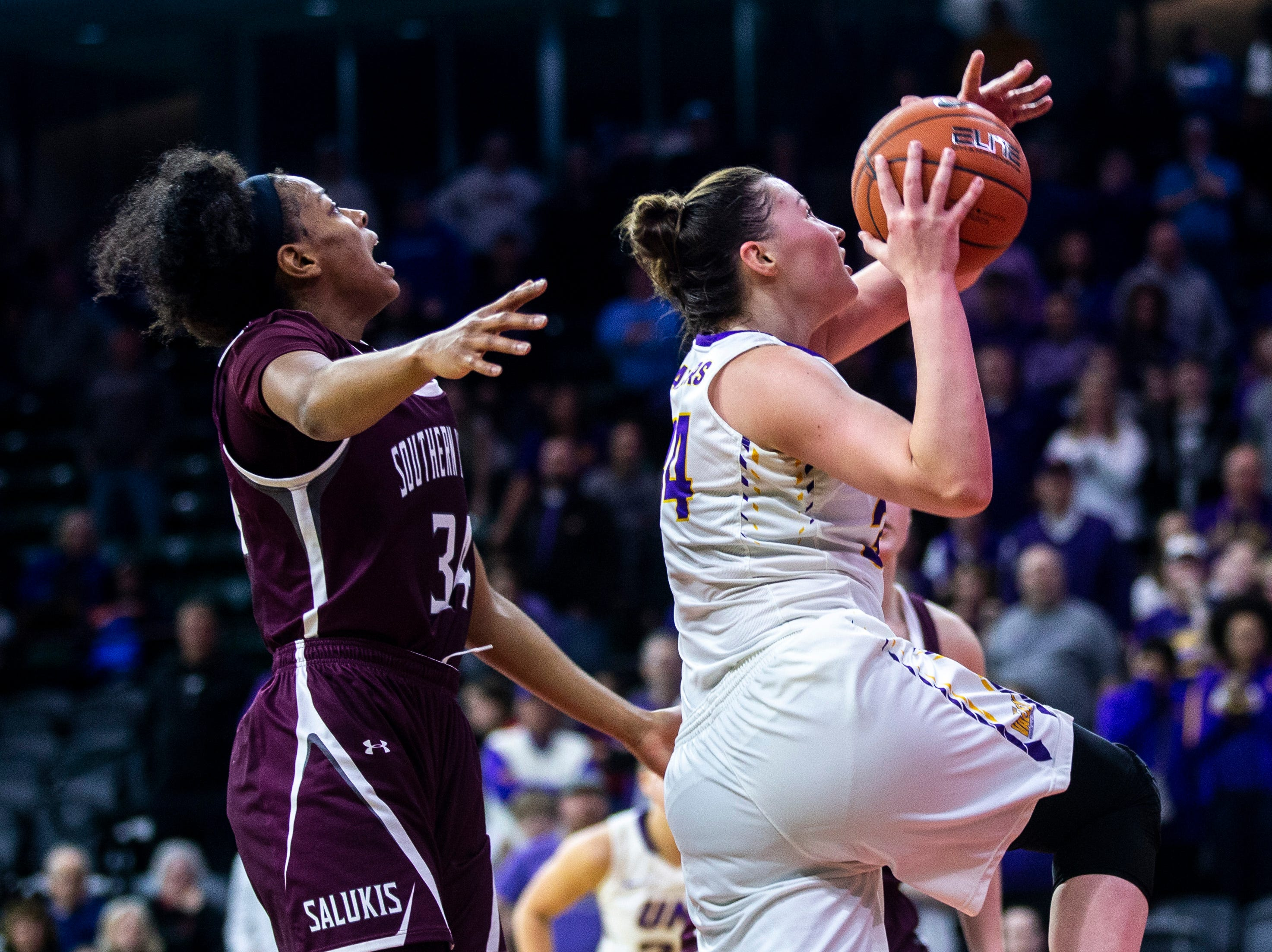 Northern Iowa forward Taylor Hagen drives to the basket past Southern Illinois forward Nicole Martin, left, during a NCAA Missouri Valley Conference women's basketball quarterfinal tournament game, Friday, March 15, 2019, at the TaxSlayer Center in Moline, Illinois.