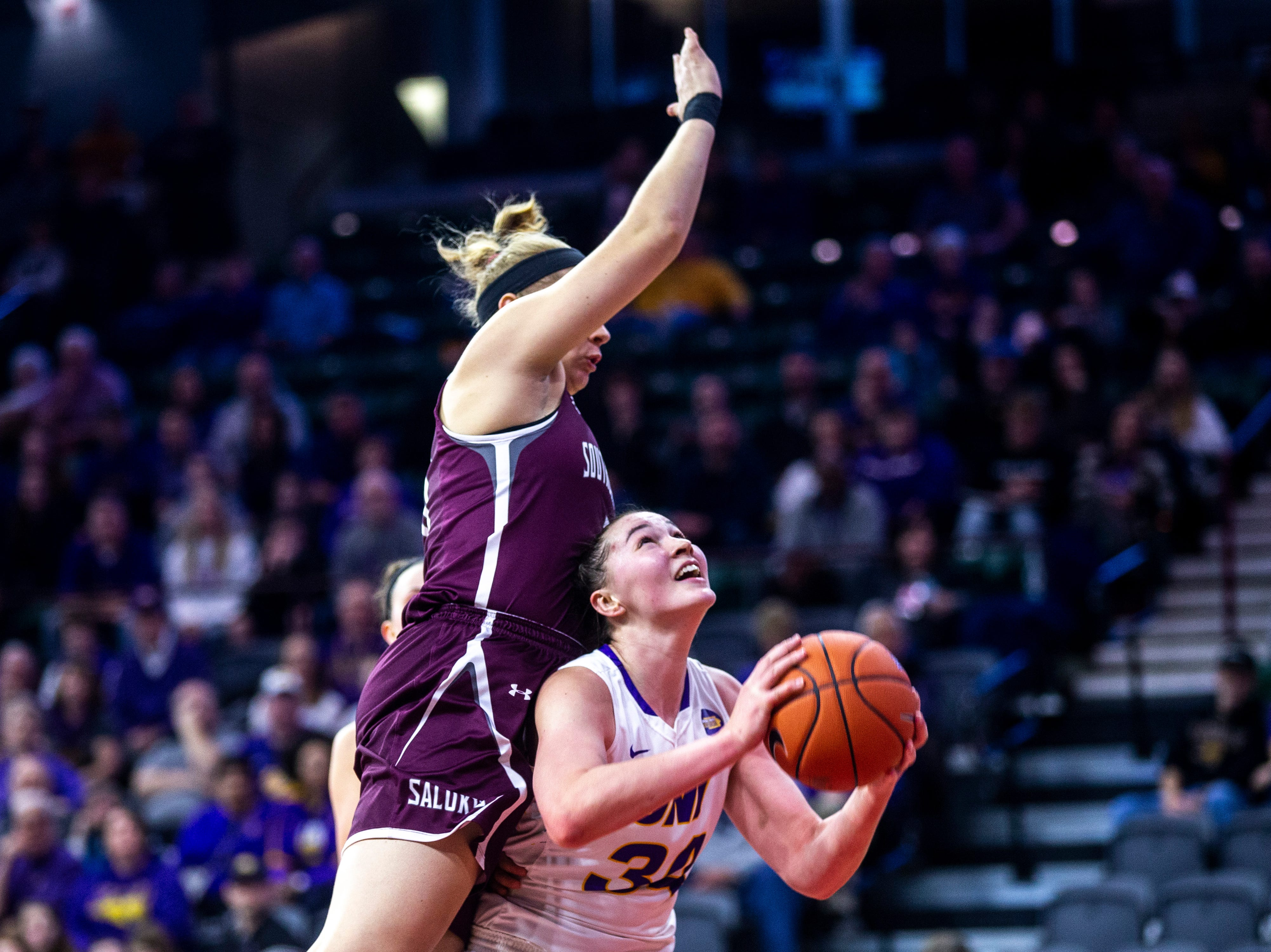 Northern Iowa forward Taylor Hagen (34) gets fouled by Southern Illinois forward Abby Brockmeyer during a NCAA Missouri Valley Conference women's basketball quarterfinal tournament game, Friday, March 15, 2019, at the TaxSlayer Center in Moline, Illinois.