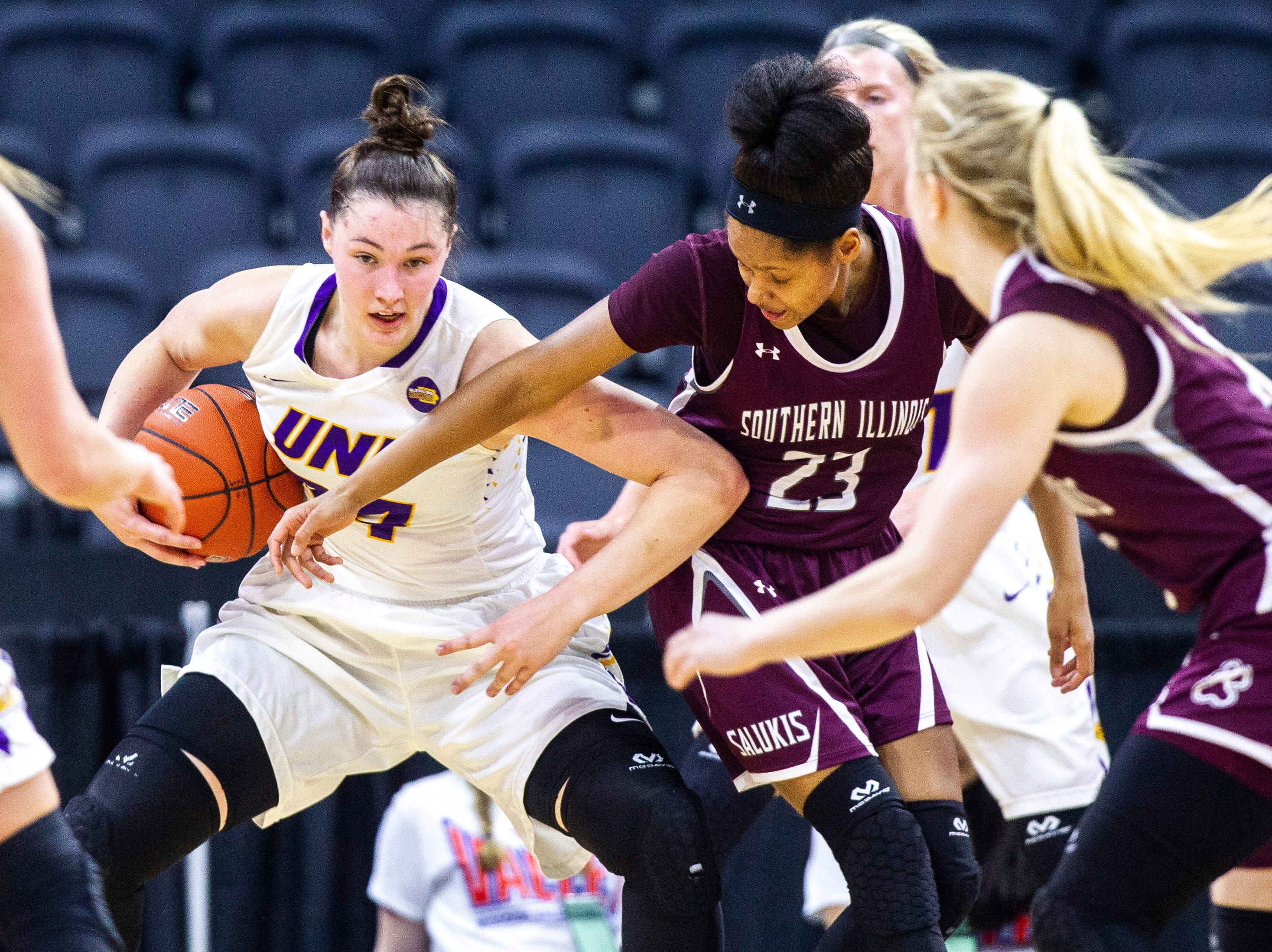 Northern Iowa forward Taylor Hagen (34) pulls down a rebound against Southern Illinois guard Kristen Nelson (23) during a NCAA Missouri Valley Conference women's basketball quarterfinal tournament game, Friday, March 15, 2019, at the TaxSlayer Center in Moline, Illinois.