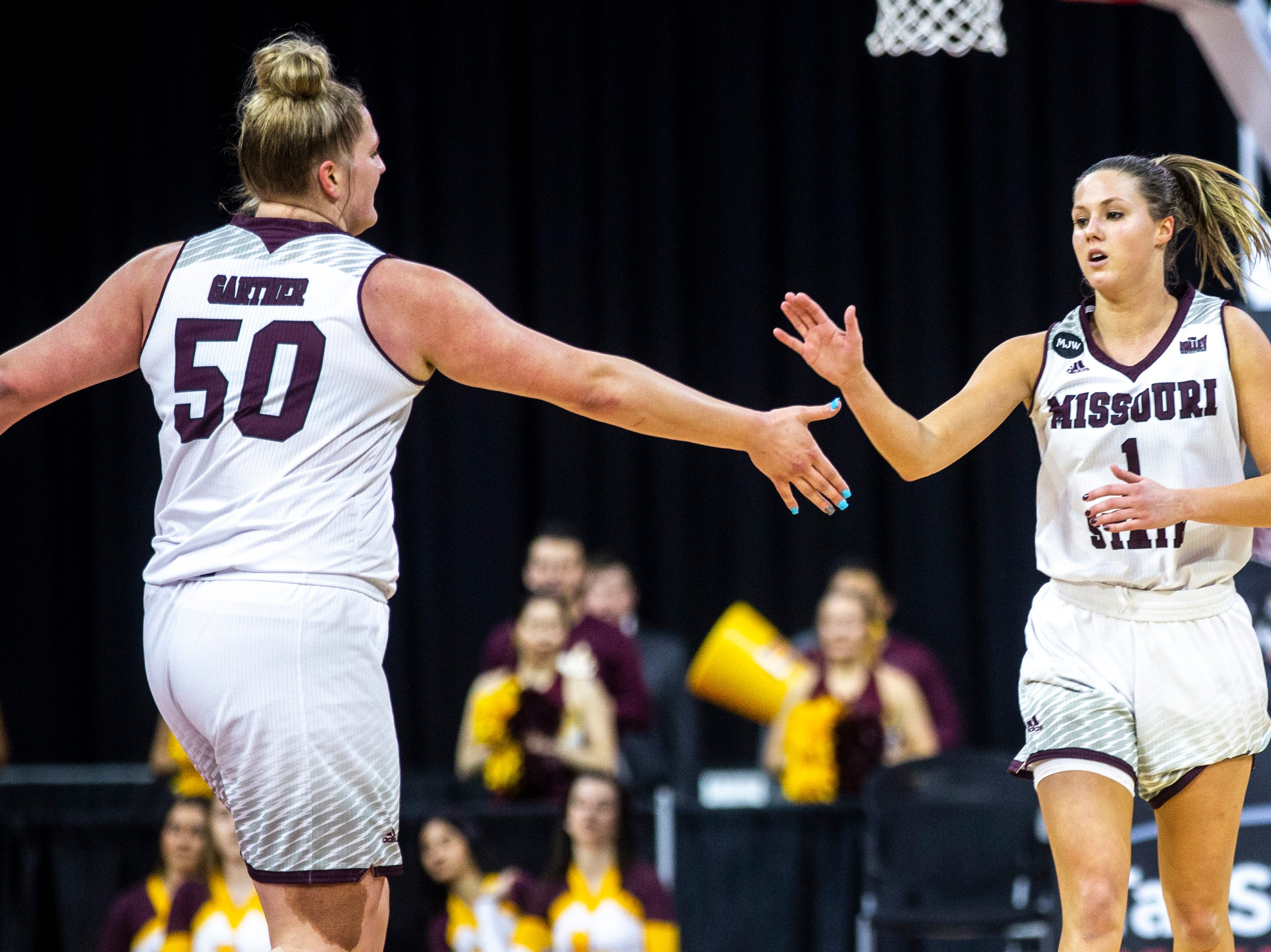 Missouri State guard Danielle Gitzen (1) gets a high-five from Missouri State center Emily Gartner (50) after making a 3-point basket during a NCAA Missouri Valley Conference women's basketball quarterfinal tournament game, Friday, March 15, 2019, at the TaxSlayer Center in Moline, Illinois.