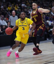 Michigan guard Zavier Simpson drives against Minnesota guard Amir Coffey during the first half action of the Big Ten tournament semifinal Saturday, March 16, 2019 at the United Center in Chicago.