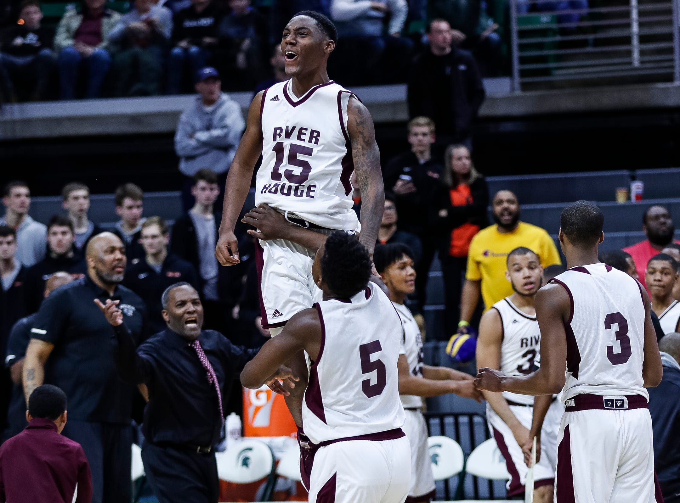 Harper Woods Chandler Park Demonte Thompson (15) is being lifted up teammate to celebrate their 72-66 win over Harper Woods Chandler Park in overtime of MHSAA Division 2 semifinal at the Breslin Center in East Lansing, Friday, March 15, 2019.