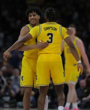 Eli Brooks and Zavier Simpson embrace during Friday's win over Iowa in Chicago.
