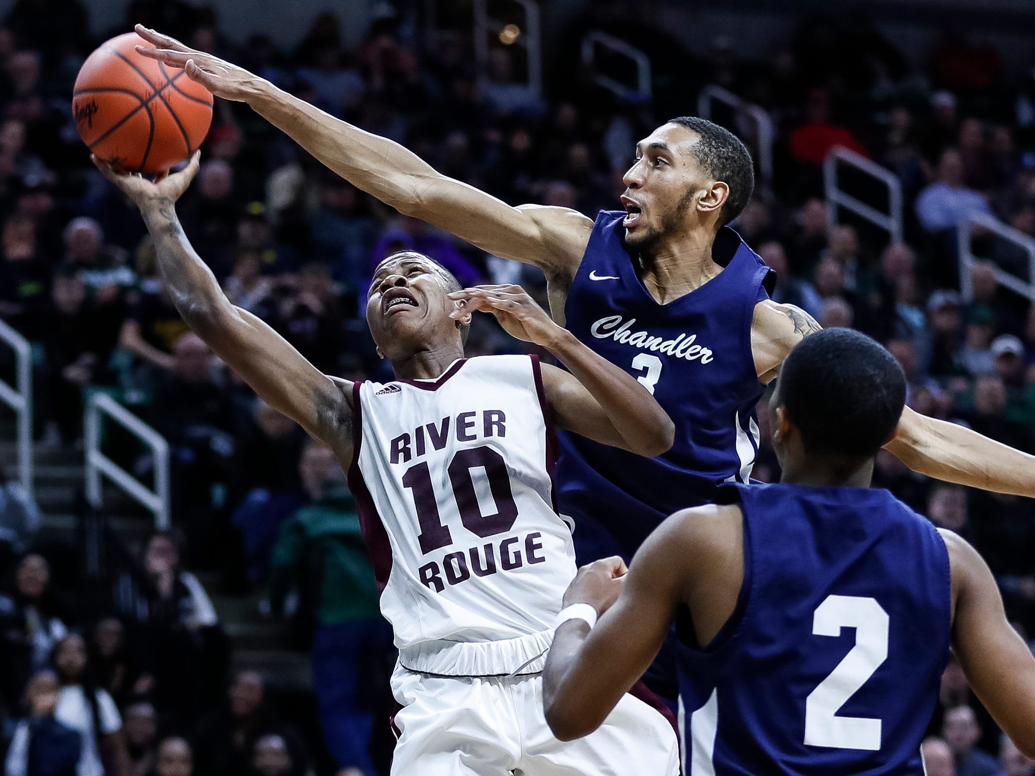 Harper Woods Chandler Park's Marquez Steele (3) blocks a layup from River Rouge's Bralin Toney (10) during the first half of MHSAA Division 2 semifinal at the Breslin Center in East Lansing, Friday, March 15, 2019.