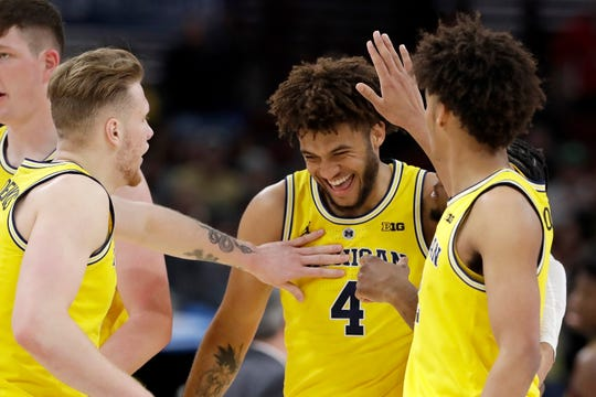 Michigan's Isaiah Livers is congratulated why his teammates after a dunk during the first half against Minnesota in the semifinals of the Big Ten Conference tournament, Saturday, March 16, 2019, in Chicago.
