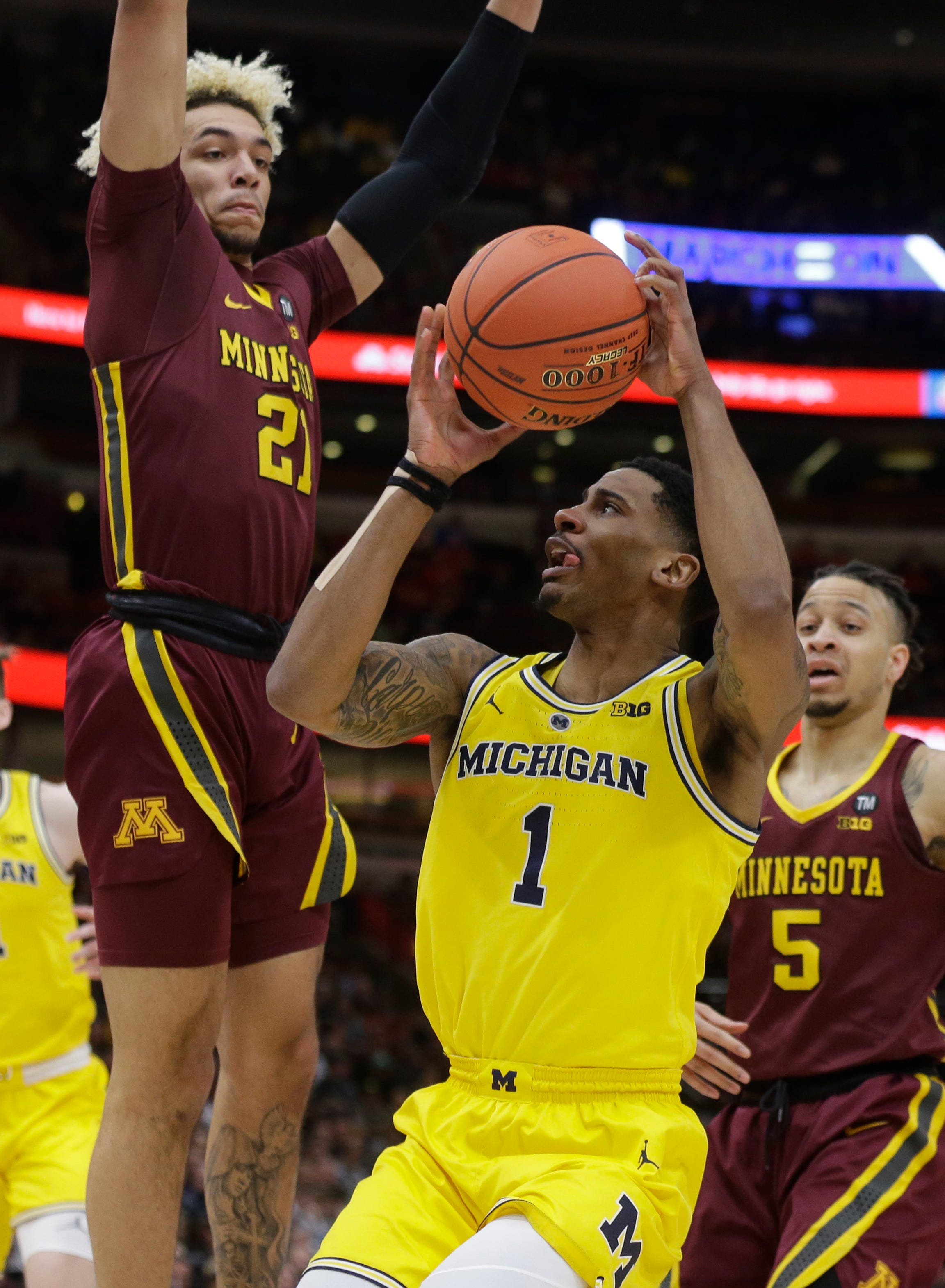 Michigan's Charles Matthews (1) drives against Minnesota's Jarvis Omersa (21) during the first half of an NCAA college basketball game in the semifinals of the Big Ten Conference tournament, Saturday, March 16, 2019, in Chicago.