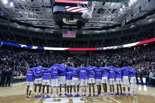 Ypsilanti Lincoln players embrace during the national anthem before the MHSAA Division 1 final against U-D Jesuit at the Breslin Center in East Lansing, Saturday, March 16, 2019.