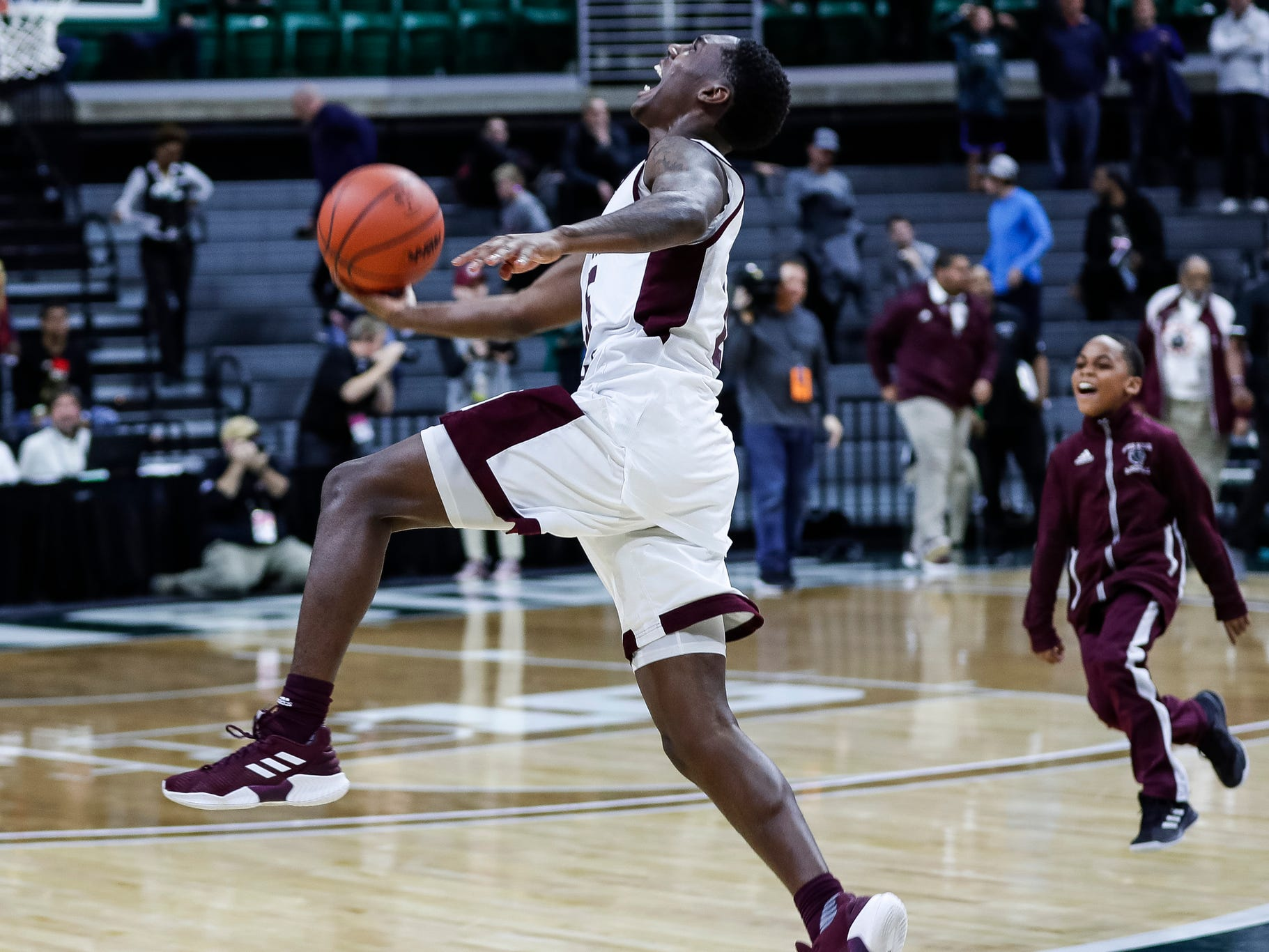 River Rouge's Kamal Hadden (15) runs across the court and throws the basketball in the air to celebrate 72-66 win over Harper Woods Chandler Park in overtime of MHSAA Division 2 semifinal at the Breslin Center in East Lansing, Friday, March 15, 2019.