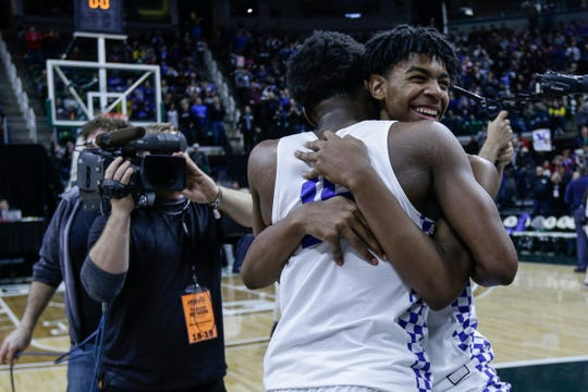 Southfield Christian players Greg Hines (15) and Malcolm King (11) hug to celebrate 63-39 win over Frankfort at the MHSAA Division 4 final at the Breslin Center in East Lansing, Saturday, March 16, 2019.