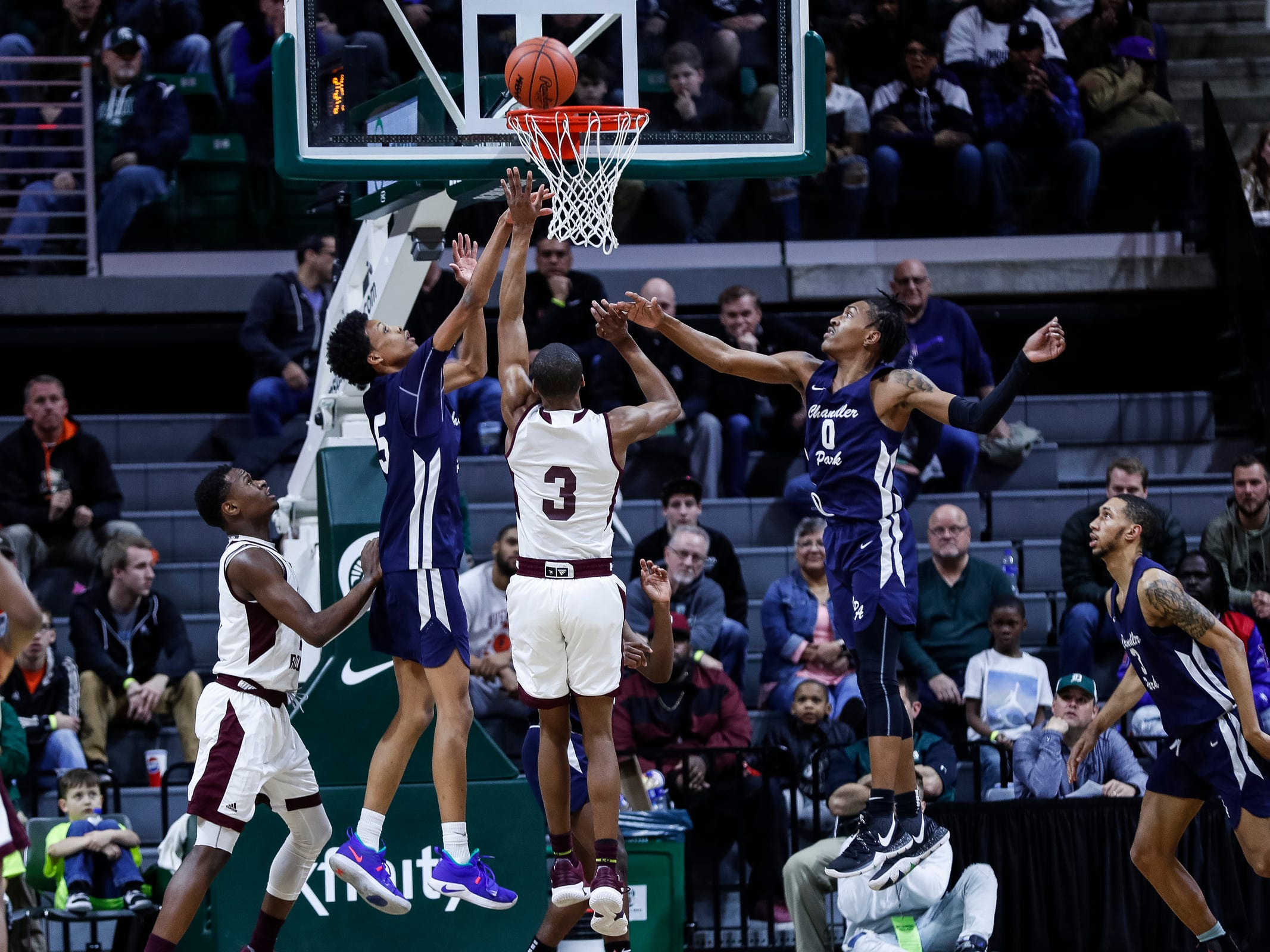 River Rouge's Micah Parrish (3) shoots against Harper Woods Chandler Park's Tyland Tate (5) and Andre Bradford (0) during the first half of MHSAA Division 2 semifinal at the Breslin Center in East Lansing, Friday, March 15, 2019.