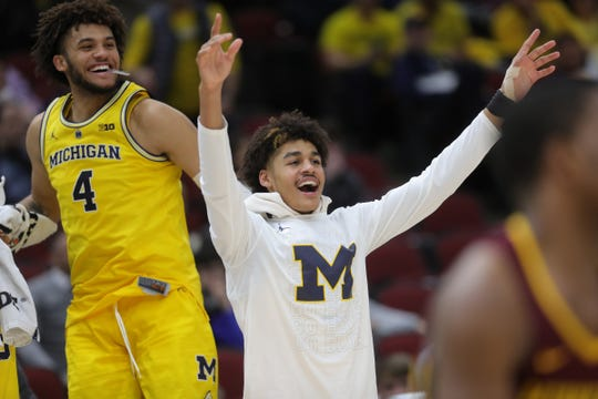 Jordan Poole, right, and Isaiah Livers watch the final seconds of the 76-49 win against Minnesota on Saturday.