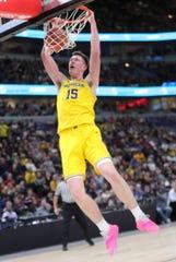 Jon Teske dunks against Iowa in the first half of the Big Ten tournament Friday in Chicago.