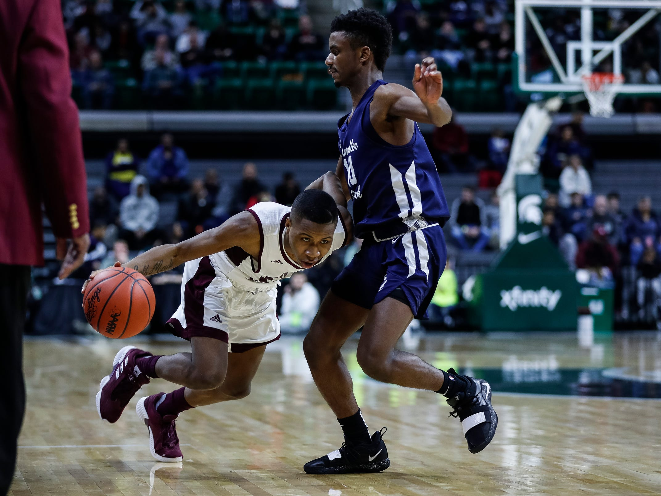 River Rouge's Bralin Toney (10) dribbles against Harper Woods Chandler Park's Josh Diggs (10) during the second half of MHSAA Division 2 semifinal at the Breslin Center in East Lansing, Friday, March 15, 2019.