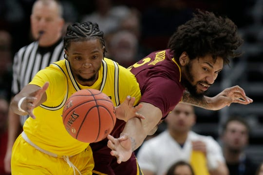 Michigan's Zavier Simpson, left, and Minnesota's Jordan Murphy battle for a loose ball during the first half of an NCAA college basketball game in the semifinals of the Big Ten Conference tournament, Saturday, March 16, 2019, in Chicago.