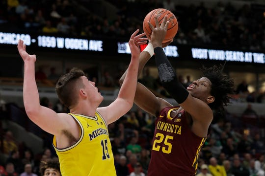 Michigan's Jon Teske (15) blocks a shot by Minnesota's Daniel Oturu (25) during the first half of an NCAA college basketball game in the semifinals of the Big Ten Conference tournament, Saturday, March 16, 2019, in Chicago.