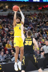 Isaiah Livers hits a 3-pointer against Iowa's Connor McCaffery in the first half.
