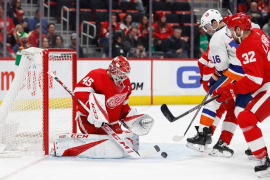 Detroit Red Wings goaltender Jonathan Bernier makes a save against New York Islanders left wing Andrew Ladd (16) during the third period at Little Caesars Arena, March 16, 2019.