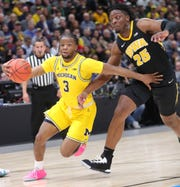 Zavier Simpson drives against Iowa's Tyler Cook on Friday.